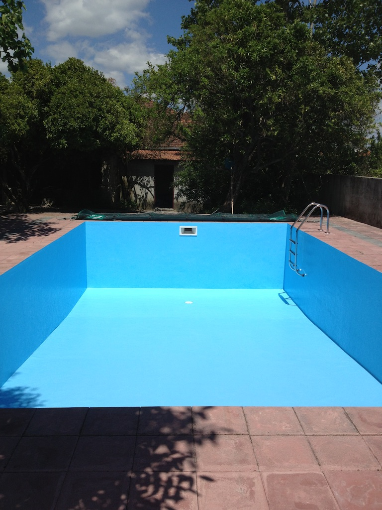 The final coat of blue paint is on the swimming pool